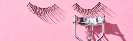 Photo pour panoramic shot of false eyelashes and eyelash curler on pink background - image libre de droit