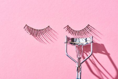 Photo pour top view of false eyelashes and eyelash curler on pink background - image libre de droit