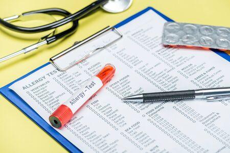 Foto de test tube and pen on allergy test results near stethoscope on yellow - Imagen libre de derechos