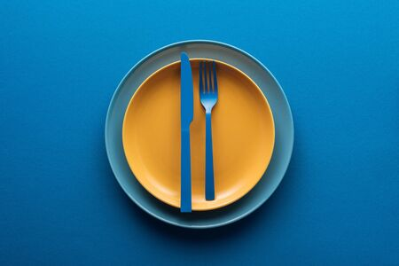 Photo for top view of blue plastic knife and fork on yellow plate above another plate on blue background - Royalty Free Image