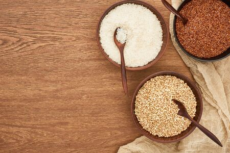 Foto de top view of bowls with white rice, roasted and raw buckwheat on wooden surface with canvas - Imagen libre de derechos