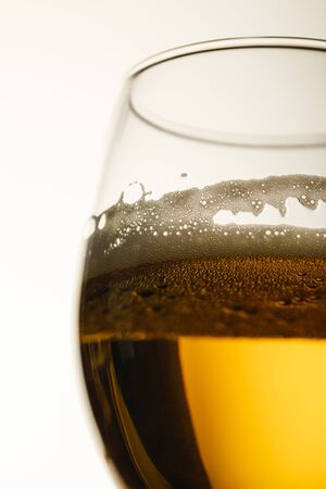Foto de close up view of glass of beer with foam and bubbles isolated on white - Imagen libre de derechos