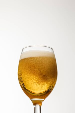 Foto de low angle view of glass of beer with foam isolated on white - Imagen libre de derechos