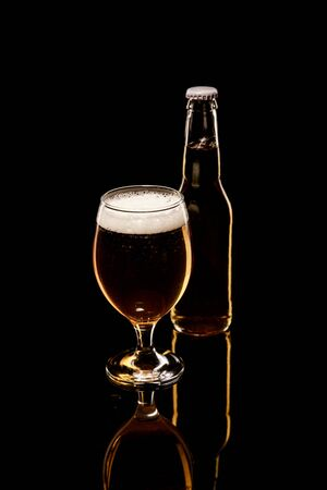 Foto de bottle and glass of beer with white foam and bubbles isolated on black - Imagen libre de derechos