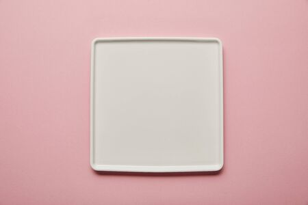 Photo pour Top view of white square flat plate on pink background - image libre de droit