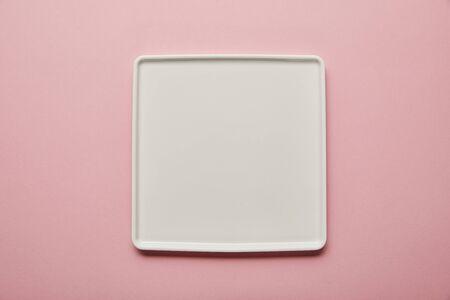 Foto de Top view of white square flat plate on pink background - Imagen libre de derechos