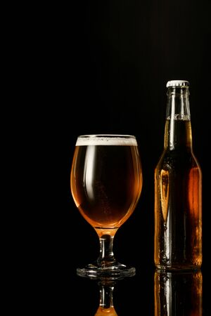 Foto de glass of beer with foam near bottle isolated on black - Imagen libre de derechos