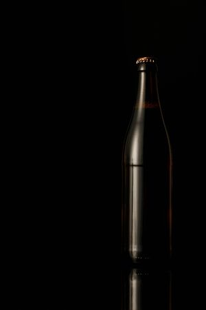 Foto de dark glass bottle of beer isolated on black - Imagen libre de derechos
