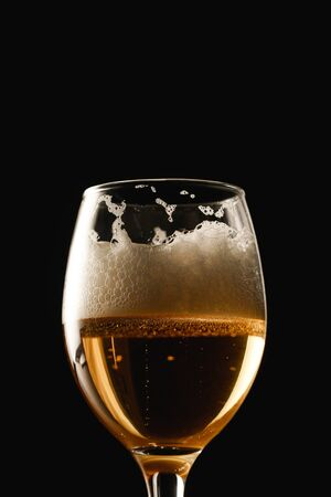 Foto de glass of beer with white foam isolated on black - Imagen libre de derechos