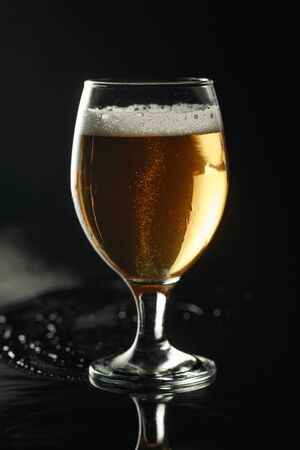 Foto de glass of beer with foam on wet surface isolated on black - Imagen libre de derechos