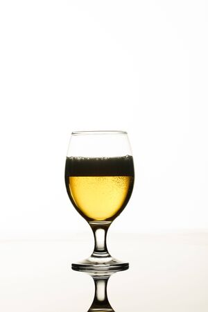 Foto de glass of beer with foam and back light isolated on white - Imagen libre de derechos