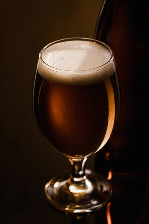 Foto de close up view of beer with white foam in glass on dark background with lighting - Imagen libre de derechos