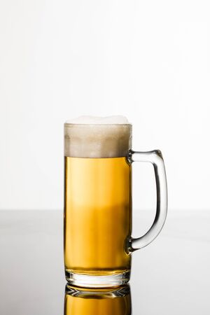 Foto de glass of beer with foam isolated on white - Imagen libre de derechos