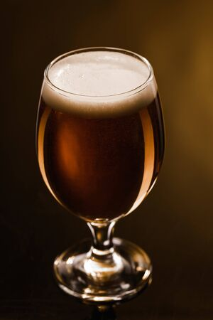 Foto de close up view of beer with foam in glass on dark background with lighting - Imagen libre de derechos