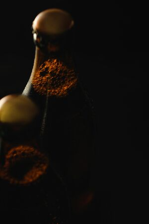 Foto de close up view of glass bottles of beer with bubbles isolated on black - Imagen libre de derechos