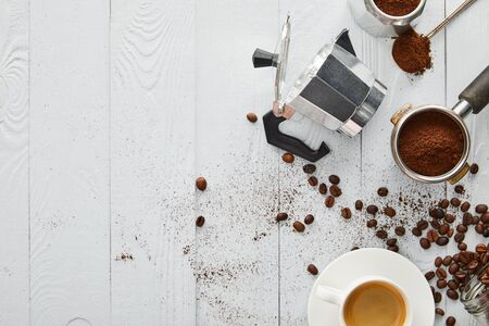Foto de Top view of geyser coffee maker near portafilter, spoon and cup of coffee on white wooden surface with coffee beans - Imagen libre de derechos