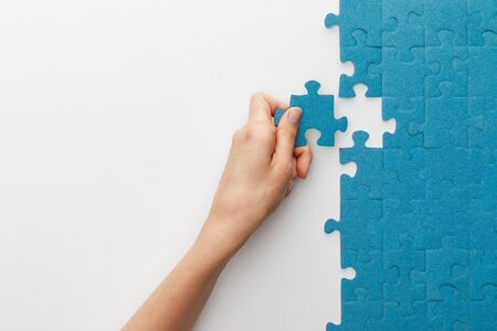 Photo pour cropped view of woman attaching blue jigsaw puzzle on white background - image libre de droit