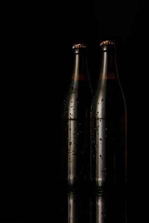 Foto de glass bottles of beer with drops isolated on black - Imagen libre de derechos