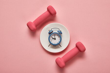 Foto de top view of dumbbells and plate with toy alarm clock on pink background - Imagen libre de derechos