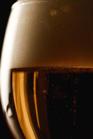 Foto de close up view of beer with foam isolated on black - Imagen libre de derechos