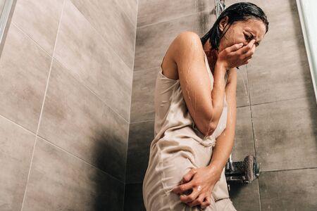 Foto de lonely sad woman crying in shower at home with copy space - Imagen libre de derechos