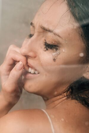 Foto de lonely depressed woman in shower covering mouth and crying at home - Imagen libre de derechos