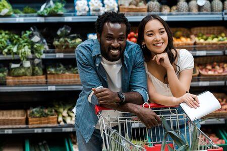 Photo pour cheerful interracial couple smiling in supermarket near shopping cart - image libre de droit