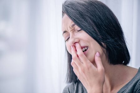 Foto de selective focus of depressed brunette woman covering mouth and crying at home - Imagen libre de derechos