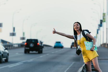 Foto de beautiful and asian woman in yellow overalls hitchhiking and holding map - Imagen libre de derechos