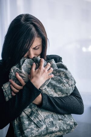 Foto de depressed woman crying and holding military clothing at home - Imagen libre de derechos