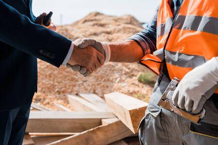 Foto de cropped view of constructor and businessman shaking hands - Imagen libre de derechos