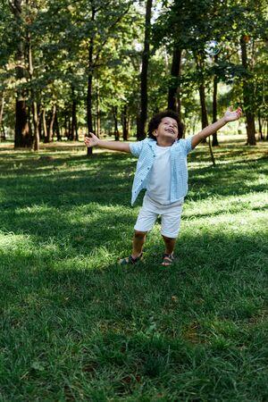 Foto de happy african american kid with outstretched hands in park - Imagen libre de derechos