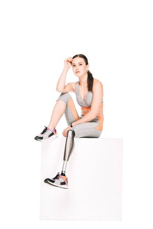 Foto per disabled sportswoman with prosthetic leg sitting isolated on white - Immagine Royalty Free