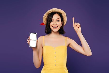 Foto de KYIV, UKRAINE - JULY 3, 2019: excited girl in straw hat showing idea gesture and holding smartphone with gmail app isolated on purple - Imagen libre de derechos