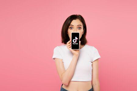 Foto de KYIV, UKRAINE - JULY 3, 2019: shocked girl holding smartphone with tiktok logo isolated on pink - Imagen libre de derechos