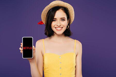 Foto de KYIV, UKRAINE - JULY 3, 2019: smiling girl in straw hat holding smartphone with netflix app isolated on purple - Imagen libre de derechos