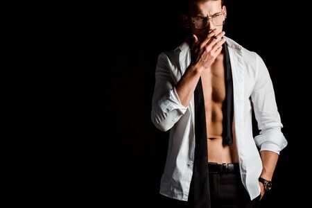 Photo pour sexy man in suit smoking isolated on black - image libre de droit
