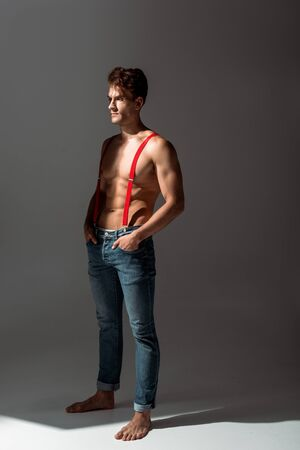 Photo for shirtless and handsome man touching red suspenders while standing on grey - Royalty Free Image
