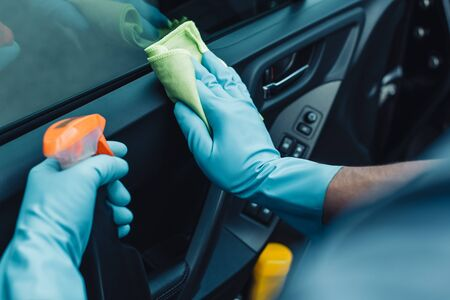 Foto de cropped view of car cleaner holding rag and spray bottle while cleaning car door - Imagen libre de derechos