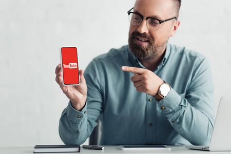 Foto de KYIV, UKRAINE - AUGUST 27, 2019: handsome businessman in shirt pointing with finger at smartphone with youtube logo - Imagen libre de derechos