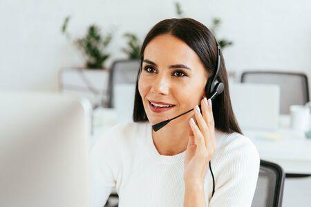 Foto de selective focus of attractive broker touching headset while working in call center - Imagen libre de derechos