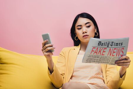 Photo pour serious asian woman holding newspaper with fake news and smartphone on yellow sofa isolated on pink - image libre de droit
