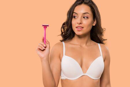 Foto de attractive woman holding pink shaving razor isolated on beige - Imagen libre de derechos