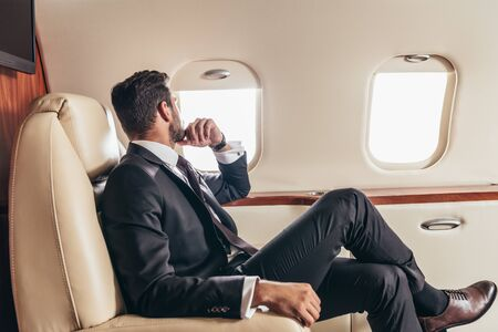 Photo for back view of businessman in suit looking through window in private plane - Royalty Free Image