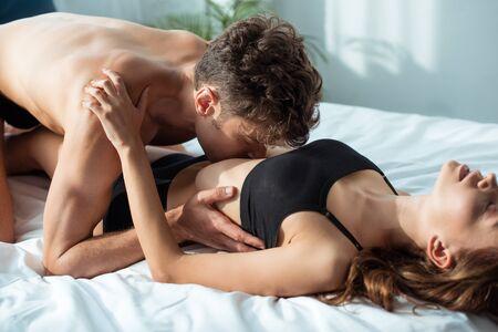 Photo pour seductive man kissing passionate girlfriend in bedroom - image libre de droit