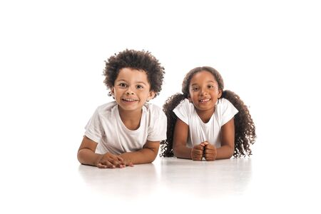 Photo pour happy african american brother and sister smiling at camera while lying on white background - image libre de droit