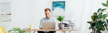 Foto de Smiling freelancer using laptop at desk in living room, panoramic shot - Imagen libre de derechos