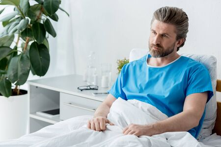 Photo for patient in medical gown sitting on bed and looking away in hospital - Royalty Free Image