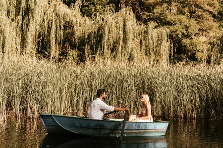 Photo for young couple in boat on river near thicket of sedge - Royalty Free Image