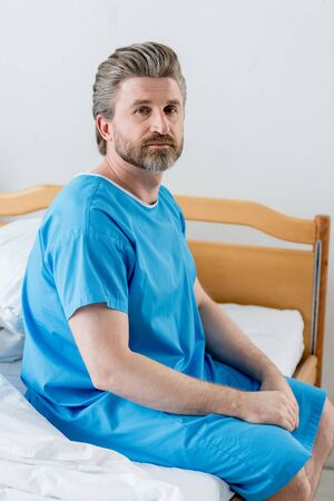 Photo for patient in medical gown sitting on bed and looking at camera in hospital - Royalty Free Image